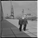 3333 Op het nieuwe kadeterrein van Wambersie en Zoon, pier 1 in de Waalhaven, wandelen burgemeester Van Walsum (links) ...