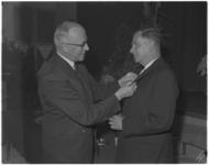 3338-1 Ir. P. Koster (rechts), chef van de Plantsoenendienst, wordt bij zijn afscheid benoemd tot officier in de orde ...