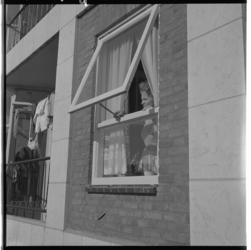3387-1 Een vrouw bekijkt het uitzicht vanuit haar woning in de nieuwe wijk 110-Morgen.