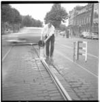 3408 In verband met door de hitte uitgezette tramrails giet een man water in de rails op Mathenesserlaan.