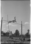 3498-1 Sportdag op atletiekbaan Nenijto met polsstokhoogspringer. De uitkijktoren van Diergaarde Blijdorp op de achtergrond.