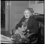 3548-2 Vrouw met poes op schoot, in een huiskamer; in kader van dierendag.