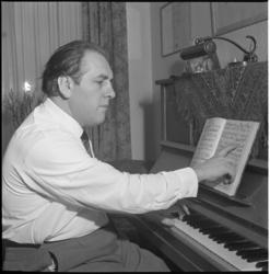 4006 Dirigent Piet Struijk, zittend voor een piano.