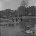 403-2 Kinderen spelen in plassen op braakliggend stukje grond