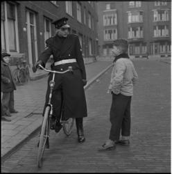 403-3 Een wijkagent op een fiets spreekt een jongen toe.