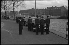 4063 Een groep uitvaartverzorgers wacht buiten bij een aantal begrafenisauto's langs de Coolhaven.