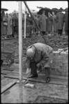 4175 De 78-jarige M. Tinbergen, gedeputeerde van de Nederduits-Hervormde Gemeente, metselt een steen van de vernielde ...