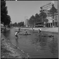 4268-2 Jongens varen op vlotten in de Westersingel. Op de achtergrond het Centraal Station en het stationspostkantoor.