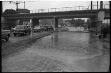 4316 Auto's rijden door grote plassen onder het spoorviaduct aan de Schiekade.