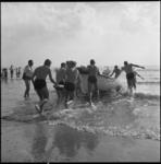 4433-1 Leden van de Rotterdamse Reddings Brigade duwen een reddingboot het water in.