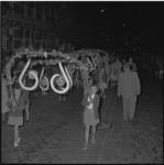 4520-1 Kinderen lopen met grote beeldmerkborden van de Floriade tijdens een lampionoptocht.