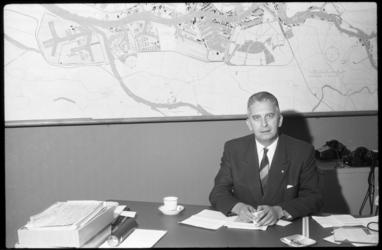 4523 Ir. F. Posthuma, directeur van het Havenbedrijf der Gemeente Rotterdam, achter een bureau. Op de achtergrond een ...
