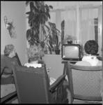 4760 Drie mensen kijken naar een tv-toestel.