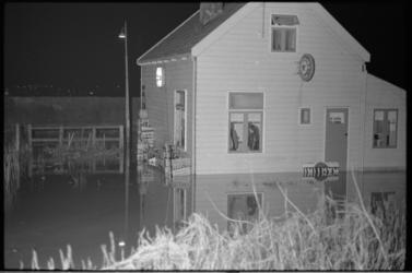 4832-1 Portier L. Bergsen van Swarttouw in een telefoongesprek in kamer met natte vloer als gevolg van dijkdoorbraakje ...