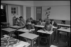 4973 Zaal met dames -aan tafeltjes- die schriftelijk examen doen.