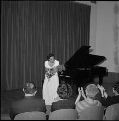 5008 Pianiste Toos Onderdenwijngaard dankt vanaf een toneel het applaudisserende publiek.