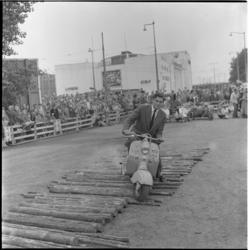 51-2 Scooterrijder bezig met rijvaardigheidstest. Op de achtergrond de noodbioscoop Lutusca.