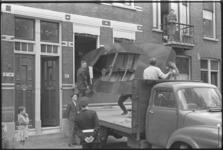 5239 Een zeilboot wordt door een raam van een woonhuis naar buiten getild en op een vrachtauto geplaatst.