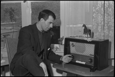 5296 Coen Moulijn zit bij de radio te luisteren naar het verslag van de voetbalwedstrijd Oost-Duitsland tegen ...