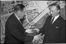 5298 Mr. J.Vink (rechts) overhandigt ir. C. van Traa de Hudig-medaille tegen de achtergrond van het Rotterdamse stadsplan.