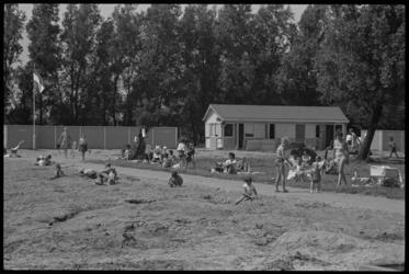 5355-2 Recreërende mensen op strandje bij het openluchtbad aan de Wilgenplas in de wijk Schiebroek.