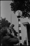 5388 Cineast met Paillard/Bolex-camera filmt beschilderde knipperbol.