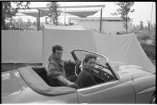 5406 Twee spelers uit musical West Side Story op de camping. Tankstation Caltex Stadhoudersweg op de achtergrond.