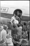 5575-2 Een invalide meisje van de Adriaanstichting wordt op de vliegtuigtrap gedragen. De kinderen kregen een ...