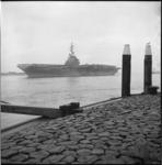 5933 Tussen het talud van een pier en hoge meerpalen zie je het vliegdekschip 'Essex' midden in de Nieuwe Waterweg liggen.