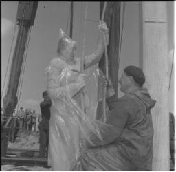 6-1 Met een plastic cape tegen oliespetters, slaat mevrouw mr. J.M. van Walsum-Quispel, de eerste paal voor scheepswerf ...