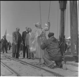6-3 Met een plastic cape tegen oliespetters, slaat mevrouw mr. J.M. Van Walsum-Quispel de eerste paal voor scheepswerf ...