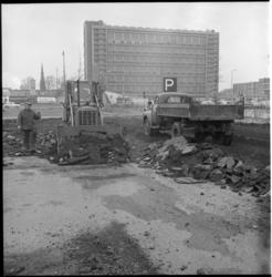 6149 Voorbereidende werkzaamheden voor de bouw van concertgebouw de Doelen.Op de achtergrond het Postgebouw PTT aan het ...