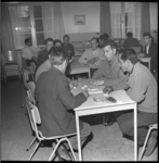 6183 Spaanse gastarbeiders zitten aan tafels in de ontspanningsruimte van verzorgingscentrum Waalhaven.