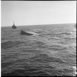 6435 Sleepboot 'Gele Zee' sleept op de Nieuwe Waterweg de, met de kiel naar boven drijvende, romp van de Thuntanker 7.