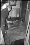 6440-1 Oudere in bed i.v.m. de extreme winterse kou krijgt bezoek van man in winterjas en met hoed.