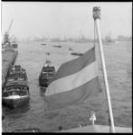 6486 Havengezicht over de Nieuwe Maas met een scheepsvlag halfstok op de voorgrond.
