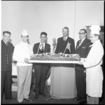 6533 Twee koks presenteren een grote taart met het getal 500 erop gespoten.