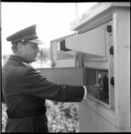 6660 Hoofdcommissaris van Politie A. Wolters bedient TV-camera bij verkeersregeling aan de zuidkant van de Maastunnel.