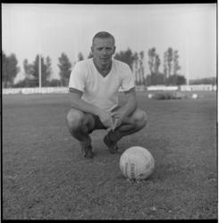 6672-1 Bob Janse, trainer van Xerxes, zit in sporttenue bij een voetbal.
