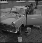 6748 Man poetst en stofzuigt een auto.