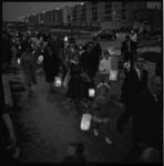 6779 Rij mensen met lampions wandelen in de avondschemering over de Spinozaweg in Lombardijen.