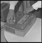 6861 Close-up van een draagbare spoelenrecorder voor geluidsopnamen. Vanaf 15-09-1964 kan men het telefoonnummer ...