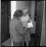 6895 Twee dames bestuderen bij twee openstaande huisdeuren een observatierapport van de 'Actie voor een Schoon Rotterdam'.