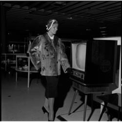 692-1 Mannequin in bontjasje passeert televisietoestel.