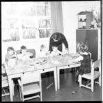 6962 Mejuffrouw J. Pot, leidster van clubhuis Het Anker, met kinderen die na schooltijd door haar worden beziggehouden.