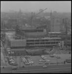 7013-1 Het in aanbouw zijnde concertgebouw De Doelen; het Rijnhotel, Stadsschouwburg en de Mauritsstraat in de wijk Cool.