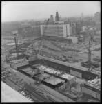 7013-2 Blik vanaf het stationspostgebouw aan de Delftsestraat over de metrobouwdokken op het Weena, het Hofplein, ...