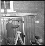 7028 Met het verven van een deur opent dominee H.Hogenhuis de bazar ten behoeve van de restauratie van de Breepleinkerk.