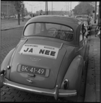 7185-4 Protestuiting met plakkaat, bevestigd op de achterzijde van een Morris-auto op het Kruisplein, van de Nationale ...