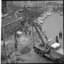 7253-2 Erasmusbeeld hangt in de takels op toenmalige Sint-Laurensplaats, nu Grotekerkplein.